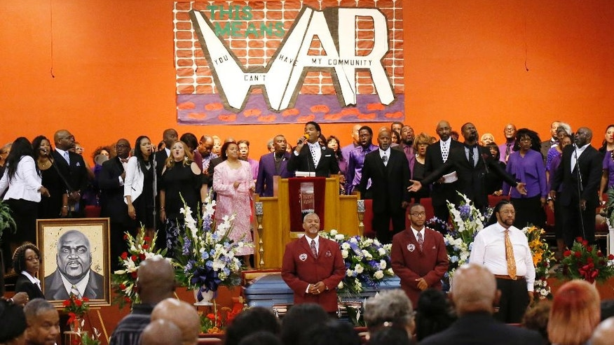 The choir sings behind the casket of Terence Crutcher during his funeral in Tulsa, Okla., Saturday, Sept. 24, 2016. Crutcher was fatally shot Sept. 16 by Officer Betty Jo Shelby. A drawing of Crutcher is at left. (AP Photo/Sue Ogrocki)