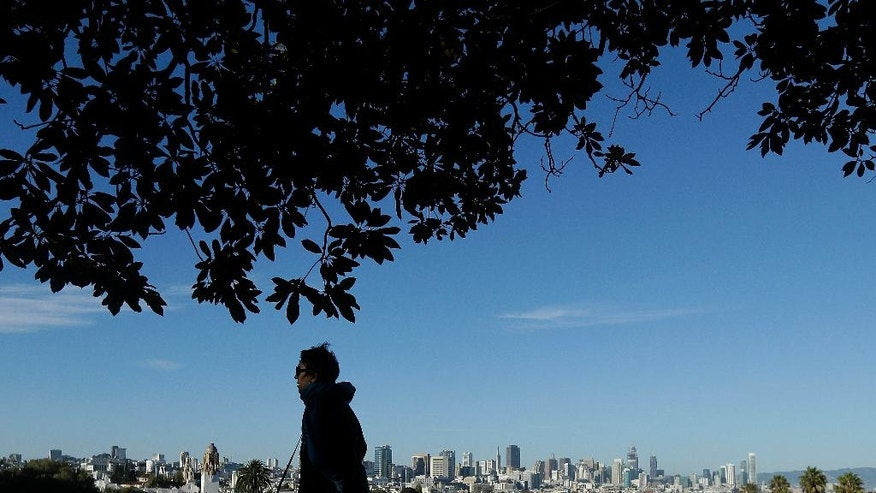 A woman walks along a path above Dolores Park with the skyline at rear in San Francisco, Friday, Sept. 23, 2016. The San Francisco Bay Area will see weekend sunshine and temperatures in the 70s and 80s. (AP Photo/Jeff Chiu)