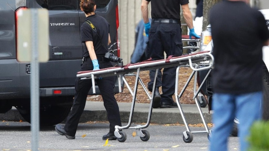 A worker carries a stretcher at the Cascade Mall Saturday, Sept. 24, 2016, in Burlington, Wash. Friday night, a man with a rifle opened fire in a Macy's Department Store at the mall, killing several people. (AP Photo/Ted S. Warren)