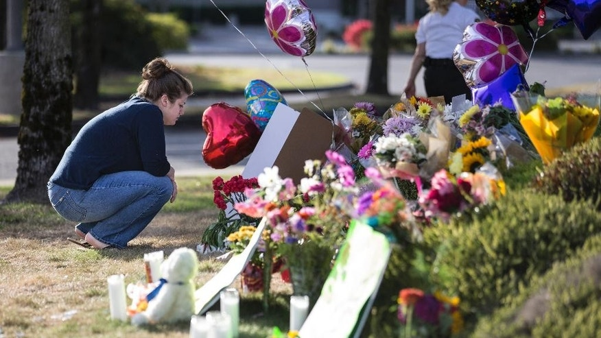 Rachel Shuler of Burlington, Wash., takes a moment after placing a sign and balloons with her stepdaughter at a makeshift memorial on Sunday, Sept. 25, 2016, in Burlington, to the victims the victims killed in a mall shooting on Friday. The 20-year-old man suspected of killing the five people with a rifle at a Macy's makeup counter had a string of run-ins with the law in recent years, including charges he assaulted his stepfather. (AP Photo/Stephen Brashear)