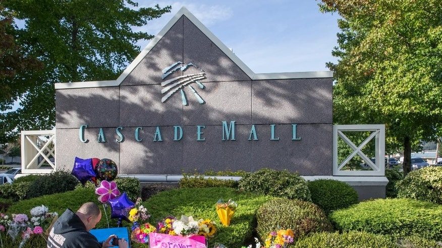 Chris Nelson of Burlington, Wash., takes a picture of a memorial on Sunday Sept. 25, 2016, in Burlington, to five victims killed in a shooting on Friday at a Cascade Mall. The 20-year-old man suspected of killing the five people with a rifle at a Macy's makeup counter had a string of run-ins with the law in recent years, including charges he assaulted his stepfather. (AP Photo/Stephen Brashear)