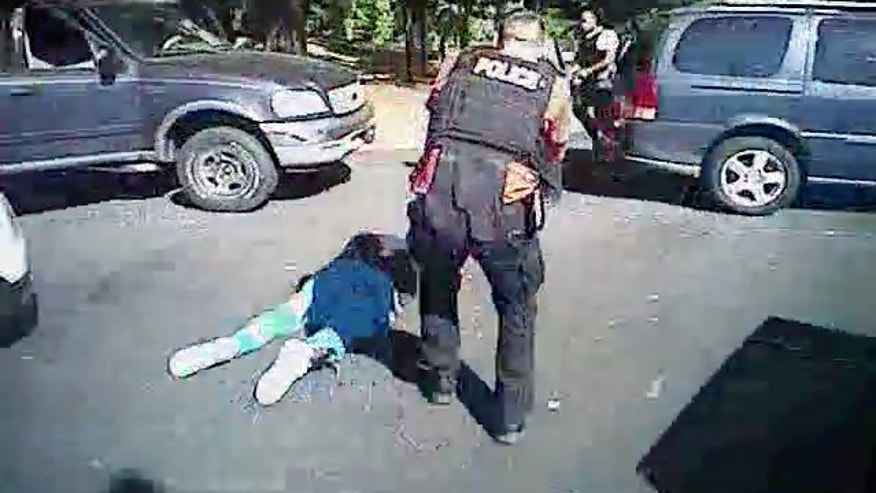 This image made from video provided by the Charlotte-Mecklenburg Police Department on Saturday, Sept. 24, 2016 shows Keith Scott on the ground as police approach him in Charlotte, N.C., on Sept. 20, 2016. (Charlotte-Mecklenburg Police Department via AP)