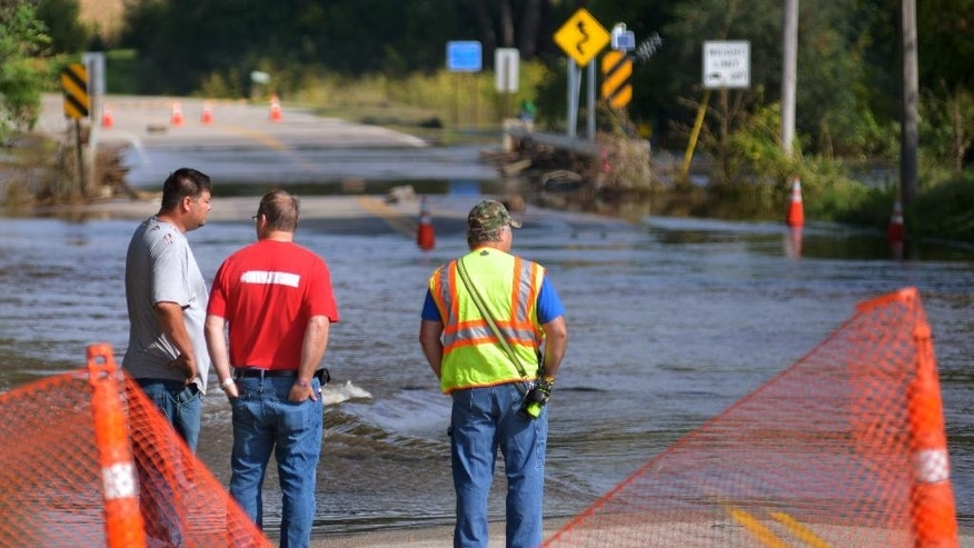 Mike Baer, left, Brad O'Donnell and Todd Huxford stand near the edge of the flooded Le Sueur River across Park Street North Saturday, Sept. 24, 2016, in St. Clair, Minn. (Bre McGee/The Free Press via AP)