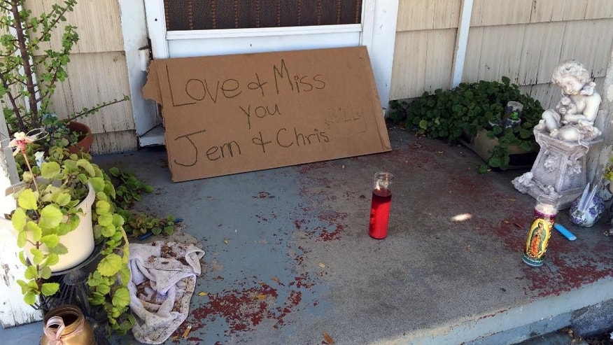A condolence note and votive candles are seen on the front porch of the home where three adults were found dead Saturday, Sept. 24, 2016, after a young child called 911 to report her parents had died, seen in Fullerton, Calif., Sunday The child placed the call about 8:20 a.m. and officers were dispatched to the home, where they found two men and a woman dead. Authorities are searching for the children's 17-year-old sibling, who is considered at risk. (AP Photo/Amy Taxin)