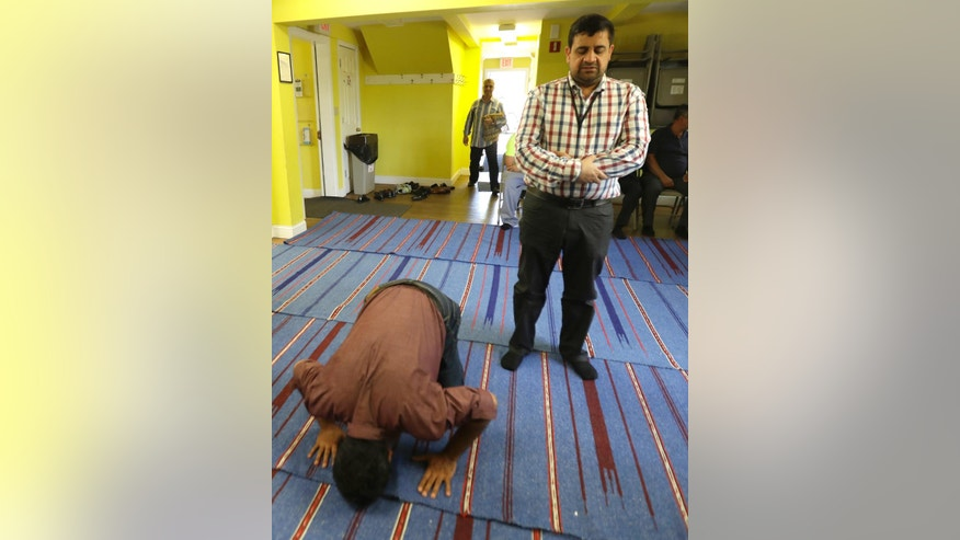 In a photo taken Friday, Sept. 23, 2016, in Basking Ridge, N.J., Shawn Butt, left, of Piscataway, N.J., prays before the start of a prayer service at the Bernards Township Community Center. The case of the New Jersey Muslim charged with planting bombs in New York and New Jersey is the latest of many challenging moments for the state's large Muslim population. They have been a target of anti-Muslim rhetoric in the presidential campaign and have seen their governor, once considered a strong ally, endorse a presidential candidate who has thrown suspicion on their entire community. (AP Photo/Julio Cortez)
