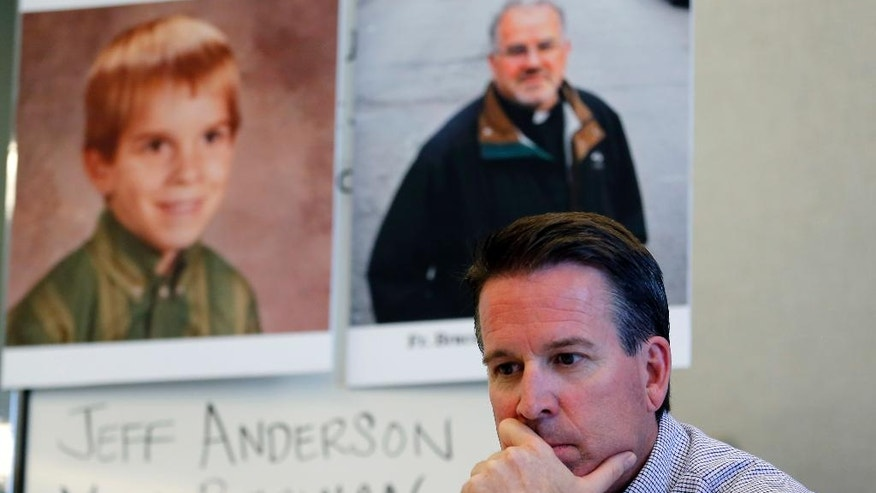 Eric Johnson listens his attorney Marc Perlman speaking during a news conference in front of his childhood portrait and Father Bruce Wellems portrait at Perlman's office Monday, Sept. 26, 2016, in Chicago. A 51-year-old Colorado man who says he was sexually abused when he was at around 7 years old by a teenager who later became a prominent Roman Catholic priest known for his work with at-risk kids on Monday sued the Chicago-based religious order to which the priest belongs, seeking the release of all records related to allegations of abuse by any of its priests. (AP Photo/Tae-Gyun Kim)