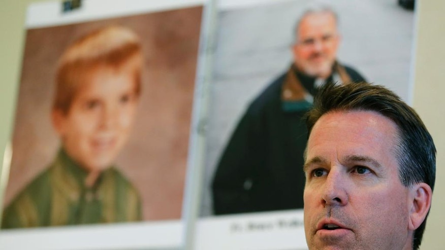 Eric Johnson speaks during a news conference in front of his childhood portrait and Father Bruce Wellems portrait at Perlman's office Monday, Sept. 26, 2016, in Chicago. A 51-year-old Colorado man who says he was sexually abused when he was at around 7 years old by a teenager who later became a prominent Roman Catholic priest known for his work with at-risk kids on Monday sued the Chicago-based religious order to which the priest belongs, seeking the release of all records related to allegations of abuse by any of its priests. (AP Photo/Tae-Gyun Kim)