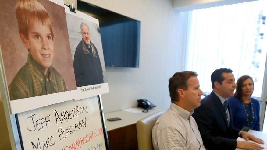 Attorney Marc Perlman, second from right, speaks during a news conference in front of young Eric Johnson's and Father Bruce Wellems' portraits at his office Monday, Sept. 26, 2016, in Chicago. A 51-year-old Colorado man who says he was sexually abused when he was at around 7 years old by a teenager who later became a prominent Roman Catholic priest known for his work with at-risk kids on Monday sued the Chicago-based religious order to which the priest belongs, seeking the release of all records related to allegations of abuse by any of its priests. (AP Photo/Tae-Gyun Kim)