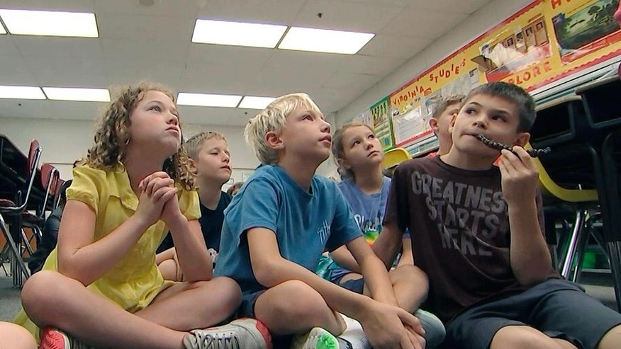 In this Tuesday, Sept. 13, 2016 still image from video, students attend the fourth grade class of Kimberly Coleman-Mitchell at Oakridge Elementary School in Arlington, Va. Elementary schools in Arlington, South Burlington, Vt., and Holyoke, Mass., are among those that went homework-free at the start of the school year. (AP Photo/Bill Gorman)