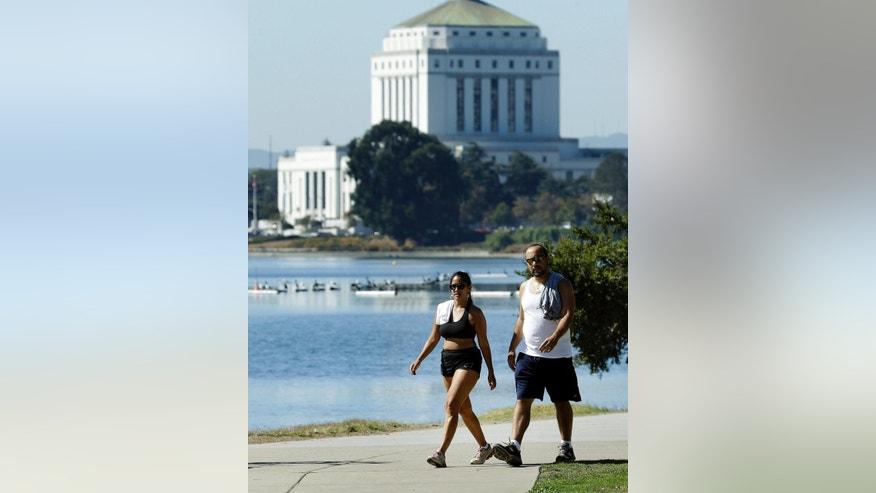 A couple walk along the shoreline of Lake Merritt on Monday, Sept. 26, 2016, in Oakland, Calif. The National Weather Service issued a heat advisory for the Bay Area with record-breaking temperatures and unhealthy air expected all day. (AP Photo/Ben Margot)