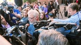 Arcan Cetin's stepfather David Marshall is swarmed by the media outside the Skagit County District Court on Monday, Sept. 26, 2016 moments after Cetin appeared in court under a magistrate's warrant which will give Skagit County prosecutors 30 days to file official charges against him in the Cascade Mall shooting where five people were murdered on Friday, Sept. 22, in Burlington. (Brandy Shreve/Skagit Valley Herald via AP)