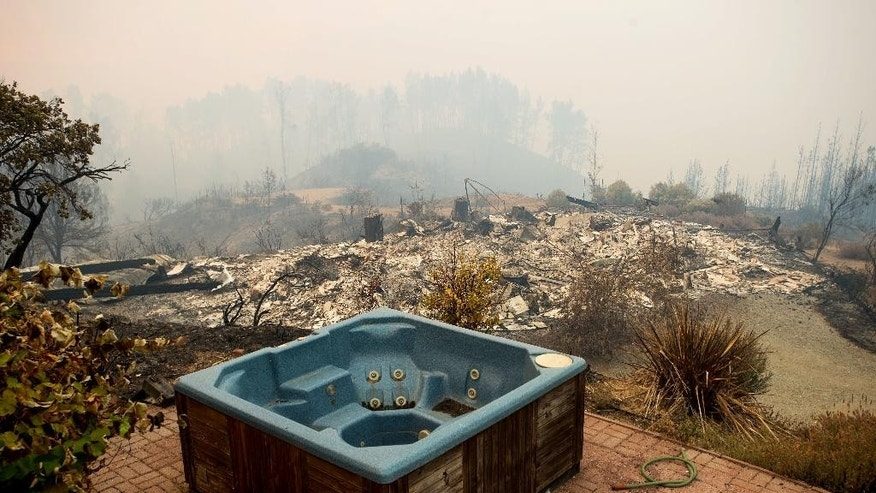 A hot tub rests in front of a residence leveled by the Loma fire along Loma Chiquita Road on Tuesday, Sept. 27, 2016, near Morgan Hill, Calif. More California residents were ordered from their homes Tuesday as a growing wildfire threatened remote communities in the Santa Cruz Mountains. (AP Photo/Noah Berger)