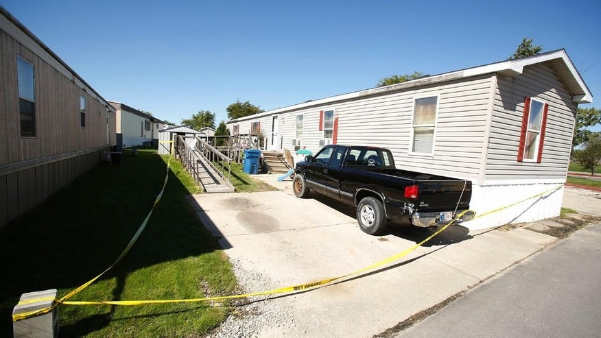 A truck sits in the driveway as crime scene tape cordons off Frank Macomber's mobile home on Tuesday, Sept. 27, 2016, after his body had been found early Tuesday morning in a wooded area near Fort Wayne, Ind.    Capt. Steve Stone of the Allen County Sheriff's Department  says authorities believe Macomber had spent some time with 29-year-old Amber Pasztor who was arrested in the deaths of her son and daughter on Monday.   (Chad Ryan/The Journal-Gazette via AP)