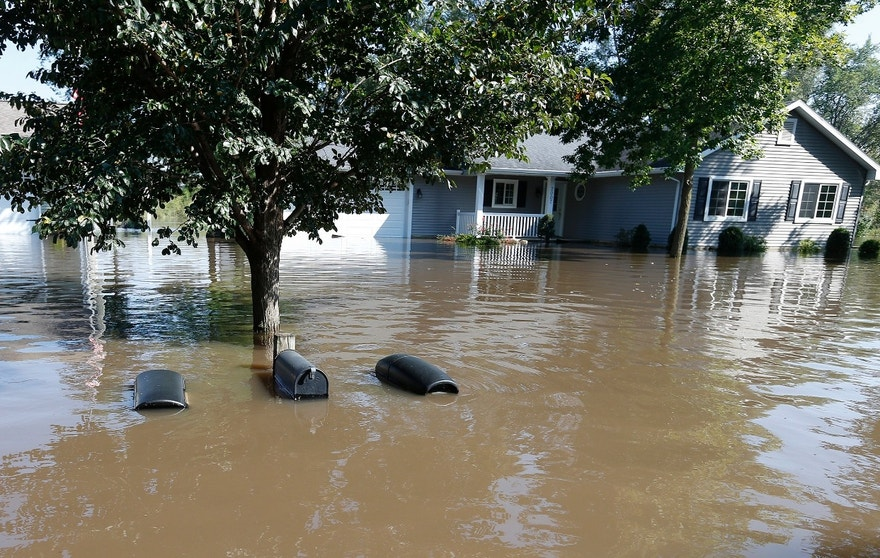 The tops of mailboxes barely break the surface of floodwaters from the Cedar River in the North Cedar neighborhood of Cedar Falls, Iowa, Saturday, Sept. 24, 2016. (Brandon Pollock/The Courier via AP)