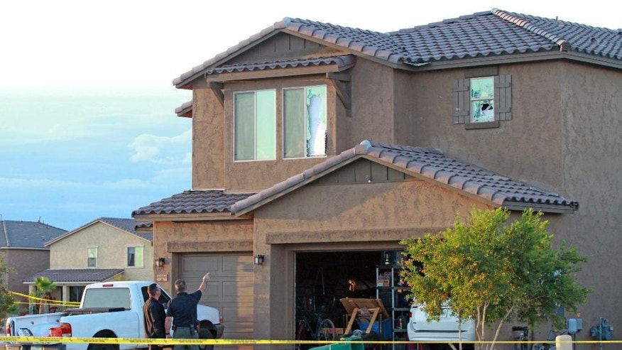 Police point to the window of a Maricopa home on Tuesday, Sept. 27, 2016, where a Border Patrol agent was found dead inside after exchanging gunfire with officers responding to a domestic violence call. Authorities said the man who allegedly fired a rifle at police responding to a 911 call made by a girl reporting domestic violence in the home has been found dead inside. (Howard Waggner/Maricopa Monitor via AP)
