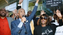 The Rev. Al Sharpton, center, and Tiffany Crutcher, right, the twin sister of Terence Crutcher, who was killed by a Tulsa police officer, raise their hands at a rally following a protest march in Tulsa, Okla., Tuesday, Sept. 27, 2016. At left is Crutcher family attorney Damario Solomon-Simmons. (AP Photo/Sue Ogrocki)