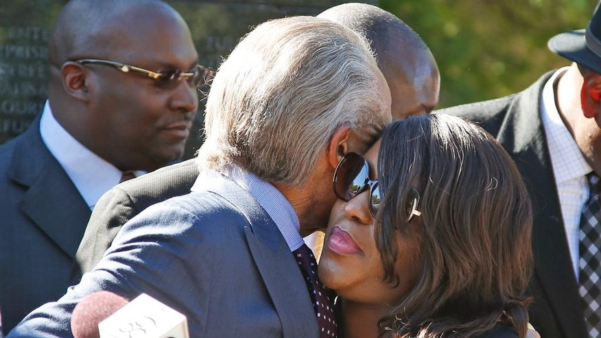 Tiffany Crutcher, right, the twin sister of Terence Crutcher, who was killed by a Tulsa police officer, embraces the Rev. Al Sharpton, left, before a protest march in Tulsa, Okla., Tuesday, Sept. 27, 2016. (AP Photo/Sue Ogrocki)
