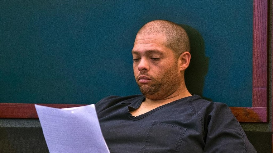 Pedro Jose Garcia reads documents as he makes his first court appearance at the Regional Justice Center in Las Vegas Wednesday, Sept. 28, 2016. A court date was postponed until Friday for the ex-felon accused of killing a Starbucks customer during a weekend coffee shop shooting in Las Vegas. (L.E. Baskow/Las Vegas Sun via AP)