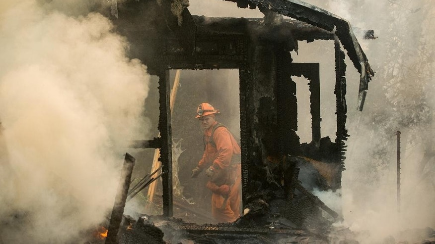 An inmate firefighter examines a burning structure while battling the Loma fire near Morgan Hill, Calif., on Wednesday, Sept. 28, 2016. (AP Photo/Noah Berger)