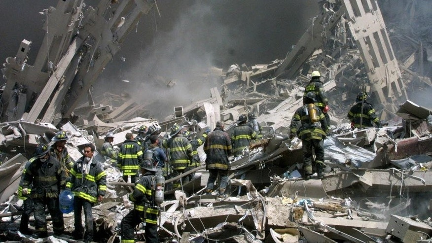 FILE - In this Sept. 11, 2001 file photo, firefighters make their way through the rubble after two airliners crashed into the World Trade Center in New York bringing down the landmark buildings. The White House lashed out at Congress on Thursday, Sept. 29, 2016, a day after Republicans and Democrats overwhelmingly overrode President Barack Obama's veto of a bill to allow families of the 9/11 victims to sue Saudi Arabia. The White House turned to mockery as top GOP leaders expressed buyer's remorse and vowed to fix the bill. (AP Photo/Shawn Baldwin/File)
