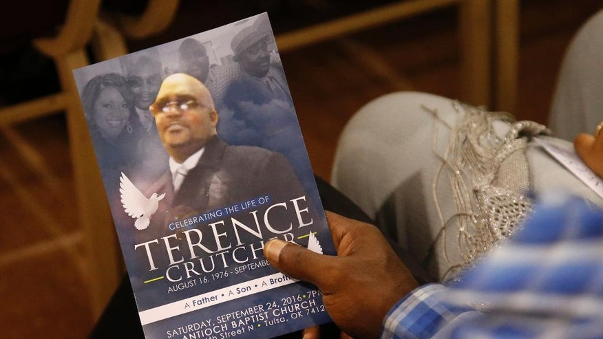 FILE - In this Sept. 24, 2016 file photo, a man holds a copy of the program for the funeral of Terence Crutcher during services to honor him in Tulsa, Okla., Crutcher was fatally shot Sept. 16 by Tulsa Police Officer Betty Shelby. Shelby's attorney Scott Wood said Thursday, Sept. 29, 2016, that she was so hyper-focused on the situation that she didn't hear other officers arrive on the scene or even the deadly gunshot she fired from her handgun. Officer Shelby, who is expected to enter a not-guilty plea at her arraignment on Friday. (AP Photo/Sue Ogrocki File)