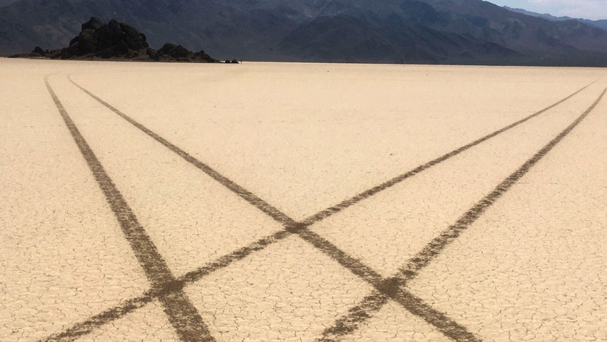 FILE - This Aug. 26, 2016 file photo provided by the National Park Service shows tire tracks made by a vehicle illegally crossing the Racetrack Playa at Death Valley National Park, Calif.