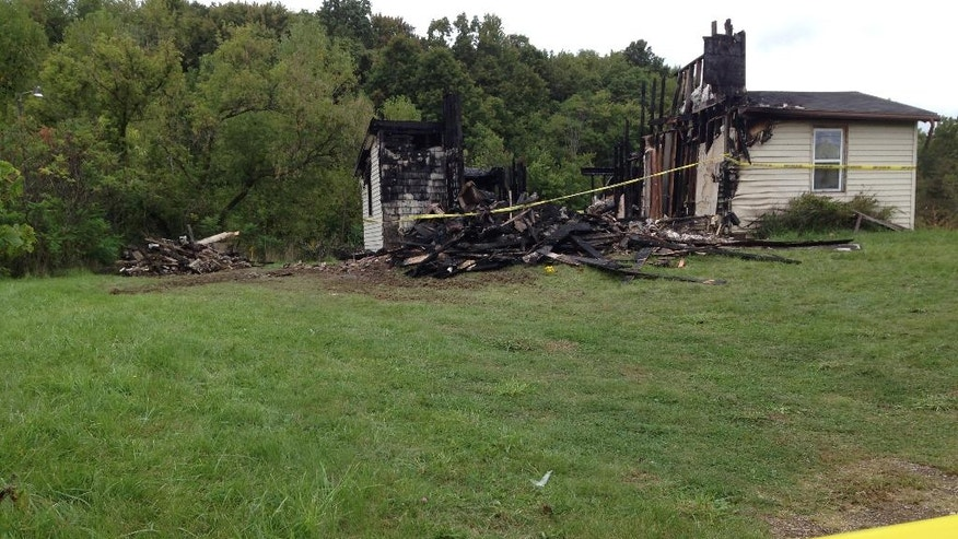 FILE – This Sept. 14, 2016, file photo shows police tape around a house partially destroyed by fire in rural Richland County, Ohio, near Mansfield, Ohio. Shawn Grate is scheduled to be arraigned Thursday, Sept. 29, 2016, in the killings of two women in Ashland, Ohio, and has pleaded not guilty. Authorities say Grate confessed to killing another woman in June 2016 at a Richland County, Ohio, house damaged in a fire later that month, and killing a woman around 2005, and he is charged in the abduction of a woman rescued Sept. 13, 2016, in Ashland, Ohio. (AP Photo/Ann Sanner, File)