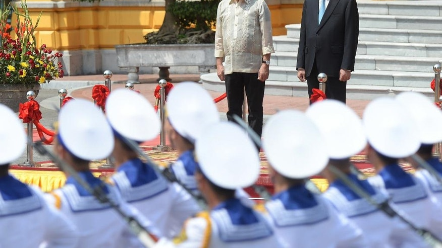 Philippine President Rodrigo Duterte, left, and his Vietnamese counterpart Tran Dai Quang stand on a podium as Vietnamese sailors from an honor guard parade during a welcoming ceremony at the presidential palace in Hanoi Thursday, Sept. 29, 2016. (Hoang Dinh Nam/Pool Photo via AP)