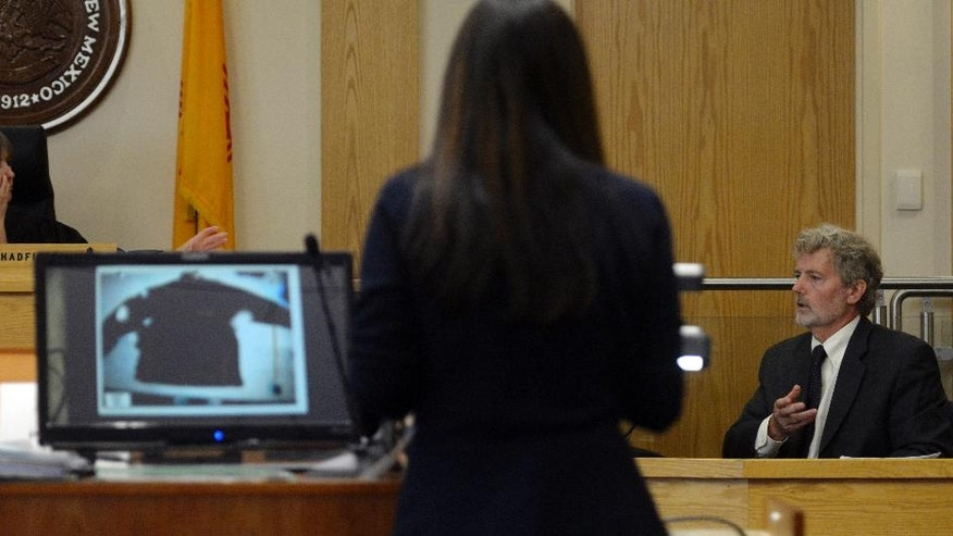 In this Monday, Sept. 26, 2016, photo, Barie Goetz, the state's crime scene reconstructionist, right, looks at photos of James Boyd's clothing on screens projected by special prosecutor Elicia Montoya, center, in order to explain a bullet trajectory to the jury during the trial of now-retired Detective Keith Sandy and former Officer Dominique Perez in the shooting death of homeless camper James Boyd in District Court in Albuquerque, N.M. (Greg Sorber/The Albuquerque Journal via AP, Pool)