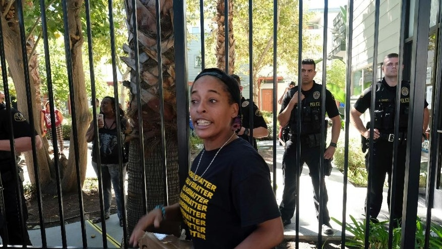 Jasmine Abdullah protests the police outside of Orange Grove Gardens Apartment complex while detectives investigate the death of a black man in Pasadena, Calif., on Friday, Sept. 30, 2016. A witness says it occurred after a struggle with police. A sheriff's statement says the death of the unidentified man occurred about 2 a.m. Friday but gives no details. (AP Photo/Richard Vogel)