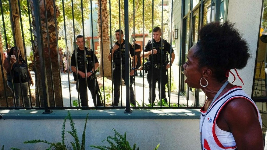 A protestor stands outside the front of Orange Grove Gardens as police stand guard during the investigation of the death of a black man at the apartment complex in Pasadena, Calif., on Friday, Sept. 30, 2016. A witness says the man's death occurred after a struggle with police. A sheriff's statement says the death of the unidentified man occurred about 2 a.m. Friday but gives no details. (AP Photo/Richard Vogel)