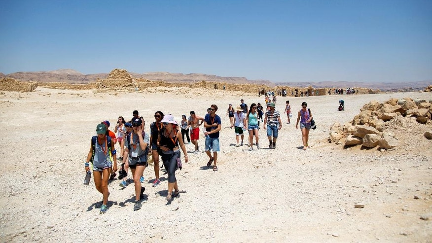 In this 2015 photo provided by Birthright Israel, a Birthright Israel group tours Masada, the ancient fortress on a plateau in the desert overlooking the Dead Sea in Israel. Birthright Israel offers free trips to Israel for young Jewish adults ages 18 to 26. Since its inception in 1999, more than 500,000 young Jewish adults from around the world have taken Birthright trips. About three-fourths of participants are American. The program is funded by the Israeli government, Jewish nonprofit organizations and philanthropists.  (Sylvie Rosokoff via AP)