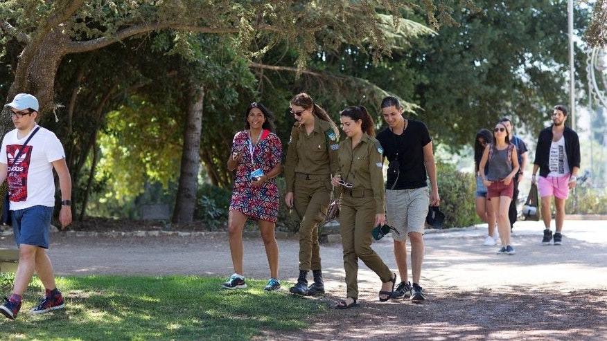 In this 2015 photo provided by Birthright Israel, a Birthright Israel group tours Mount Herzl, the site of Israel's national cemetery. Birthright Israel offers free trips to Israel for young Jewish adults ages 18 to 26. Since its inception in 1999, more than 500,000 young Jewish adults from around the world have taken Birthright trips. About three-fourths of participants are American. The program is funded by the Israeli government, Jewish nonprofit organizations and philanthropists. (Sylvie Rosokoff via AP)