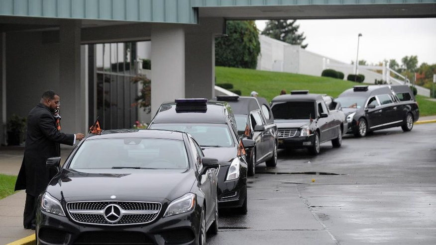 Ozie Pye, III, owner of O.H. Pye, III Funeral Home, puts funeral flags on his vehicle in front of four hearses before the service for four siblings alleged killed in their Dearborn Heights home by Gregory Green, a father to two of the children and a step-father to the two others, Friday, Sept. 30, 2016, in Farmington Hills, Mich. (Todd McInturf/Detroit News via AP)
