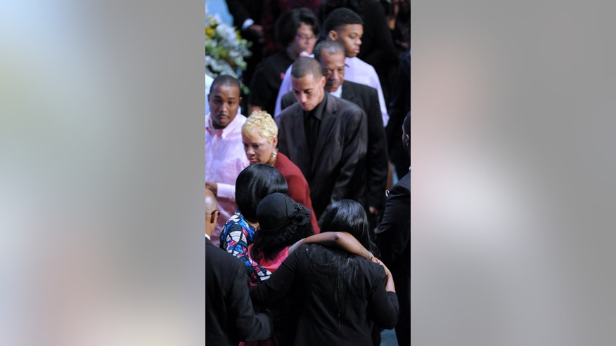 Faith Harris-Green, lower-center, is helped back to her seat before the funeral service for her four children at Detroit First Church of the Nazarene in Farmington Hills, Mich., Friday Sept. 30, 2016. The siblings were allegedly killed in their Dearborn Heights home, by Gregory Green, a father to two of the children and a step-father to the two others. Green also is accused of attacking his wife, Harris-Green.  (Todd McInturf/Detroit News via AP)