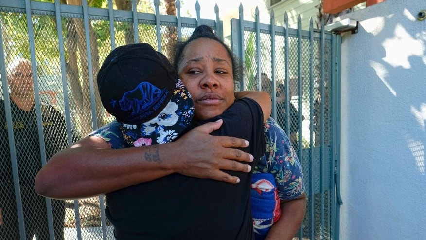 Shainie Lindsay is embraced by a friend in front of Orange Grove Gardens in Pasadena as detectives investigate the death of the father of her children, whom she said died after a struggle with police, in Pasadena, Calif., on Friday, Sept. 30, 2016. A sheriff's statement says the death of the unidentified man occurred about 2 a.m. Friday but gives no details. (AP Photo/Richard Vogel)