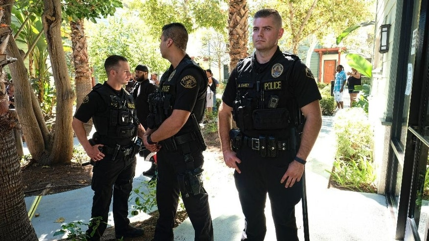 Pasadena Police officers stand guard inside the Orange Grove Gardens Apt. complex as Los Angeles County homicide detectives investigate the death of a black man in Pasadena, Calif., on Friday, Sept. 30, 2016. A witness says it occurred after a struggle with police. A sheriff's statement says the death of the unidentified man occurred about 2 a.m. Friday but gives no details.  (AP Photo/Richard Vogel)