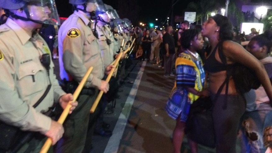 "Demonstrators yell at police during a protest Wednesday, Sept. 28, 2016, in El Cajon, Calif. Dozens of demonstrators on Wednesday protested the killing of Alfred Olango, a Ugandan refugee shot by an officer after authorities said he pulled an object from a pocket, pointed it and assumed a ""shooting stance."" (AP Photo/Julie Watson)"