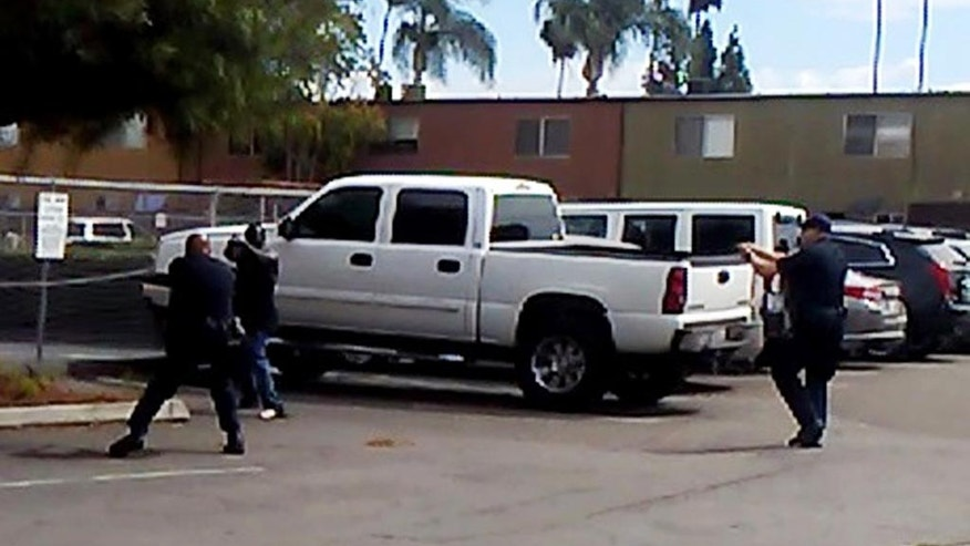 """In this Tuesday, Sept. 27, 2016 frame from video provided by the El Cajon Police Department, a man, second from left, faces police officers in El Cajon, Calif. The man reportedly acting erratically at a strip mall in suburban San Diego was shot and killed by police after pulling an object from his pocket, pointing it at officers and assuming a """"shooting stance,"""" authorities said. Some protesters claimed the man was shot with his hands raised, but police disputed that and produced the frame from cellphone video taken by a witness that appeared to show the man in the """"shooting stance"""" as two officers approached with weapons drawn. (El Cajon Police Department via AP)"""