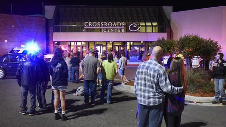 FILE - In this Saturday, Sept. 17, 2016, file photo, people stand near the entrance on the north side of Crossroads Center mall between Macy's and Target as officials investigate a reported multiple stabbing incident, in St. Cloud, Minn. Shoppers feeling unnerved by recent shooting and stabbing attacks at U.S. shopping centers may not notice huge changes, but mall operators are looking at new technologies and other measures that offer protection without intruding too much on customers. (Dave Schwarz/St. Cloud Times via AP, File)