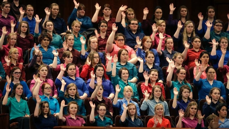 FILE - In this April 2, 2016, file photo, members of the combined Choir from BYU-Idaho raise their hands during a sustaining vote at the two-day Mormon church conference in Salt Lake City. Mormons gather for a twice-yearly conference to hear spiritual guidance from top leaders during a testy presidential election and as society grapples with issues of race and sexuality. (AP Photo/Rick Bowmer, File)
