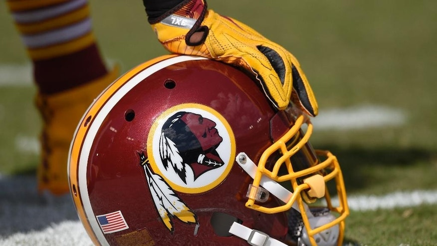 In this photo taken Sept. 18, 2016, a Washington Redskins helmet is seen on the sidelines during the first half of an NFL football game against the Dallas Cowboys in Landover, Md. The Supreme Court will hear a First Amendment challenge over the government's refusal to register offensive trademarks in a case that could affect the Washington Redskins. The justices agreed Thursday, Sept. 29, 2016, to take up a dispute involving an Asian-American rock band called the Slants, but did not act on a separate request to hear the higher-profile Redskins case at the same time.  (AP Photo/Nick Wass)