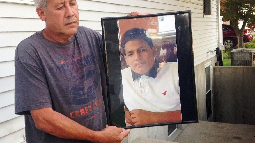 In this Sept. 27, 2016 photo, Abraham Chaparro, holds a photograph of his murdered stepson, Miguel Garcia-Moran, outside his home in Brentwood, N.Y. The remains of Garcia-Moran, who was reported missing in February, were found in September. Multiple teenagers from the same Long Island high school have been found dead and while police suspect all the deaths are related to gang violence, they are releasing few details. (AP Photo/Claudia Torrens)