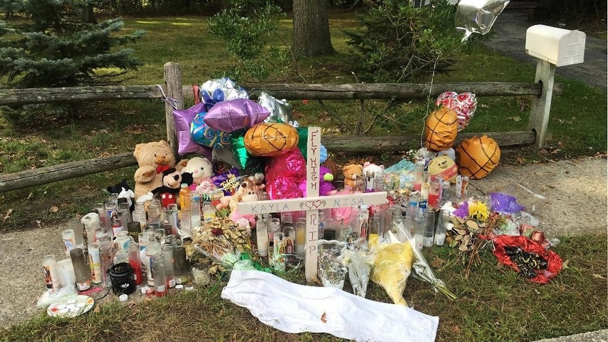 In this Sept. 27, 2016 photo, a memorial for Nisa Mickens and Kayla Cueva is located near the locations where their bodies were found in Brentwood, N.Y. The girls, who were best friends, were found murdered. Multiple teenagers from the same Long Island high school have been found dead and while police suspect all the deaths are related to gang violence, they are releasing few details. (AP Photo/Claudia Torrens)