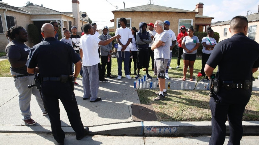 Oct. 2, 2016: Los Angeles Police officers speak to neighbors and members of the community gathered around a makeshift memorial outside a residence.