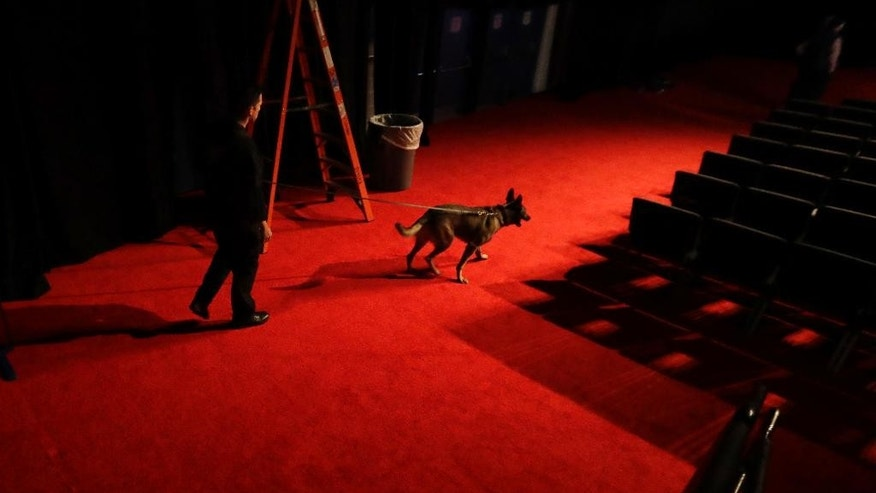 An officer walks his dog through the debate hall at Longwood University during preparations for the vice-presidential debate between Republican vice-presidential nominee Gov. Mike Pence and Democratic vice-presidential nominee Sen. Tim Kaine in Farmville, Va., Monday, Oct. 3, 2016. (AP Photo/AP Photo/Julio Cortez)