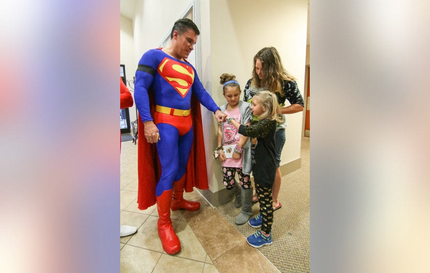 Zowie Sanders, gives a fist bump to John Suber, left, of Greenville, dressed as Superman, with her sister Lindsey Sanders, center, and their mother Brooke Starks, right, of Townville, during a wake service for Jacob Hall at Oakdale Baptist Church in Townville, S.C., Wednesday, Oct. 4, 2016. Jacob, a classmate and a teacher were shot last Wednesday as they left for recess. Authorities say the suspect, a 14-year-old boy, had shot his father to death before driving to Townville Elementary. The other student and teacher were treated and released from a hospital that day. (Ken Ruinard/The Independent-Mail via AP, Pool)