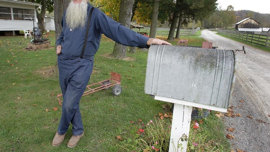 FILE - In this Oct. 10, 2011, file photo, Samuel Mullet Sr. stands in front of his home in Bergholz, Ohio. Mullet, the leader of a breakaway group that was accused in hair- and beard-cutting attacks on fellow Amish, is asking the U.S. Supreme Court to review the case. The petition was filed last month on behalf of Mullet Sr. and two of the 15 followers sentenced in the case. They're challenging the constitutionality of the federal hate crimes law, and how a kidnapping allegation was used to stiffen Mullet's sentence. (AP Photo/Amy Sancetta, File)
