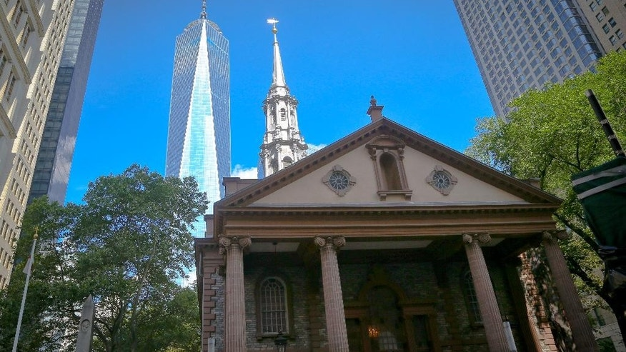 "This photo taken Tuesday Aug. 9, 2016, shows the exterior of St. Paul's Chapel in New York. The Episcopal sanctuary, Manhattan's oldest church, is getting ready to celebrate its 250-year history, which includes worshippers ranging from George Washington to those who searched for victims following the Sept. 11 attacks.  The renovation will be unveiled on its anniversary date Oct. 30, along with a ""9/11 Chapel of Remembrance"" area for quiet reflection that also contains artifacts of the attacks. One World Trade Center rises in the background. (AP Photo/Seth Wenig)"