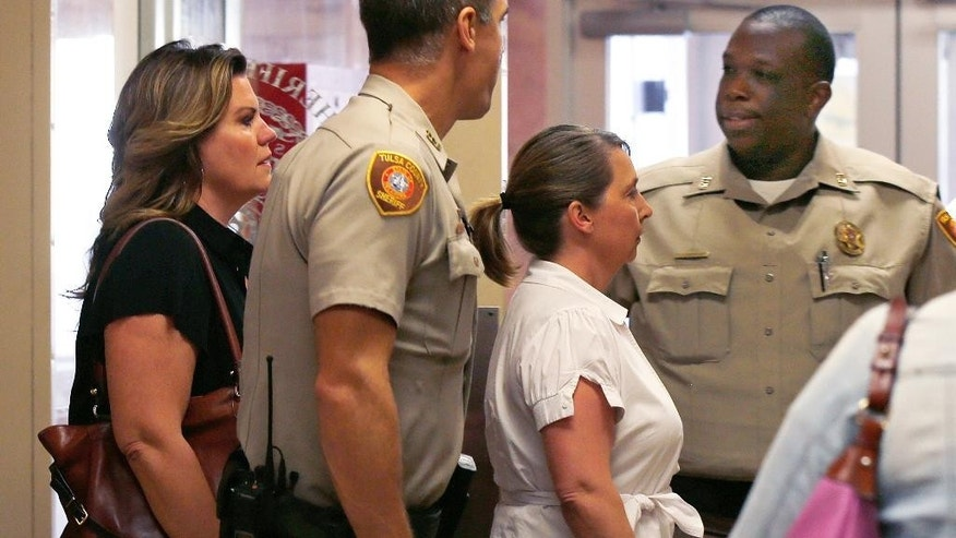 RETRANSMISSION TO CORRECT DATE OF FILE PHOTO TO SEPT. 30, 2016 - FILE - In this Friday, Sept. 30, 2016 file photo, Tulsa police officer Betty Shelby, right, is escorted from the Tulsa County Sheriff's office into a courtroom with her attorney Shannon McMurray, left, in Tulsa, Okla.,  Shelby is charged with first degree manslaughter in the Sept. 16, 2016 killing of Terence Crutcher. Attorneys representing Shelby are asking authorities to hold on to a handgun that they say Terence Crutcher may have fired a day before his death. (AP Photo/Sue Ogrocki, File)